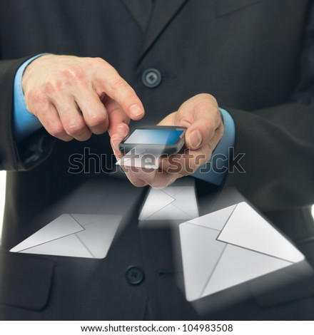 Businessman hold touch screen mobile phone and sends a virtual message - stock photo