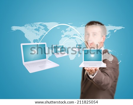 Businessman hold virtual world map with laptops - stock photo