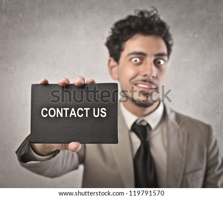 Businessman holding a black cardboard on which is written contact us - stock photo