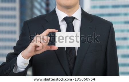 Businessman holding a blank business card - stock photo