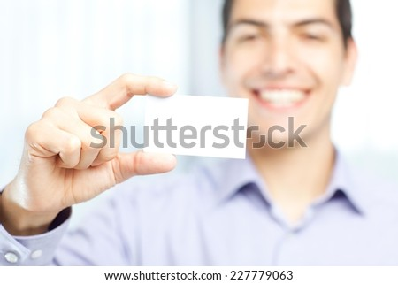 Businessman holding a blank business card and smiling. Focus on the card.