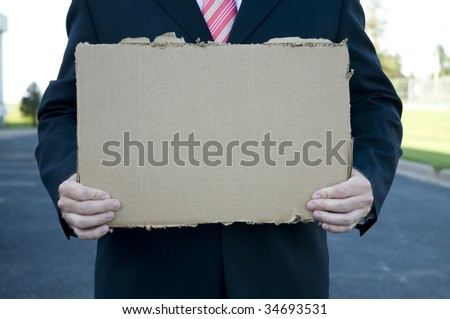 Businessman holding a blank cardboard sign - stock photo