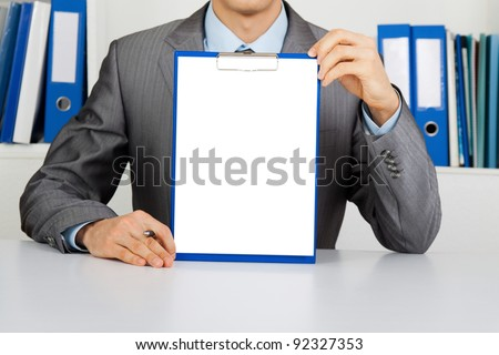 businessman holding a blank white board, signboard, clipboard with paper, showing an empty bill board with copy space for text, unrecognizable person sitting at the desk at office