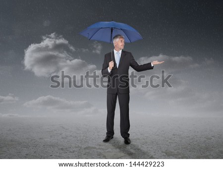 Businessman holding a blue umbrella  during a stormy weather