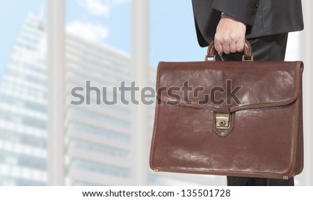 Businessman holding a briefcase in the office - stock photo