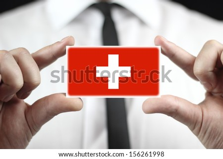 Businessman holding a business card with a Switzerland Flag - stock photo