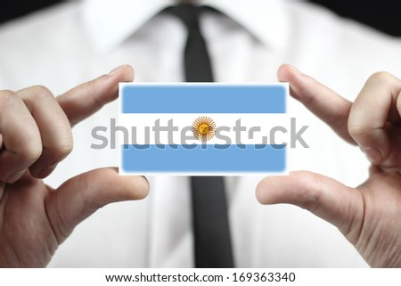 Businessman holding a business card with Argentina Flag - stock photo