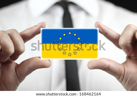 Businessman holding a business card with EU and Ukraine Flag - stock photo
