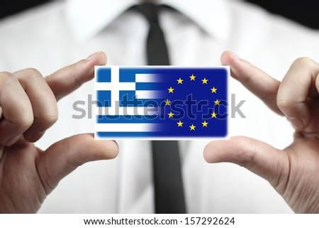 Businessman holding a business card with Greece and EU Flag - stock photo