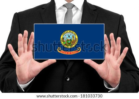 Businessman holding a business card with Idaho State Flag - stock photo