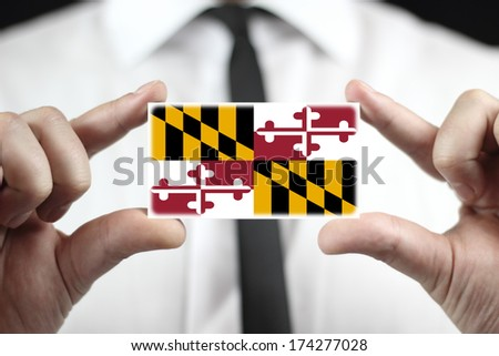 Businessman holding a business card with Maryland State Flag - stock photo