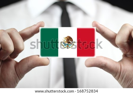 Businessman holding a business card with Mexico Flag - stock photo