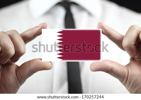 Businessman holding a business card with Qatar Flag - stock photo