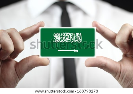 Businessman holding a business card with Saudi Arabia Flag - stock photo