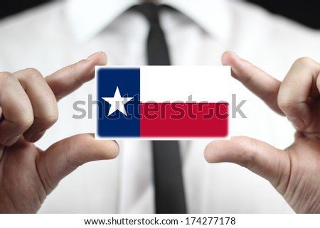 Businessman holding a business card with Texas State Flag - stock photo