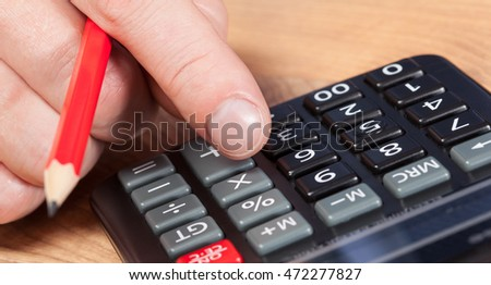 Businessman holding a calculator and a red pencil, closeup shot