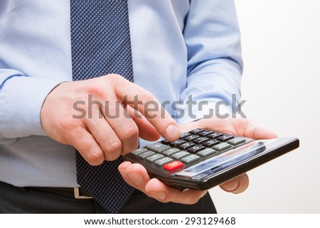 Businessman holding a calculator and counting, white background