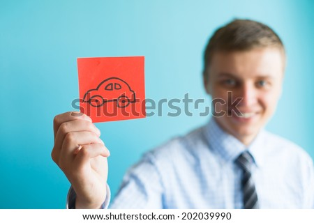 Businessman holding a car icon - stock photo