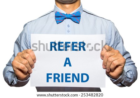 Businessman holding a card with a motivational message written on it Refer a friend - stock photo