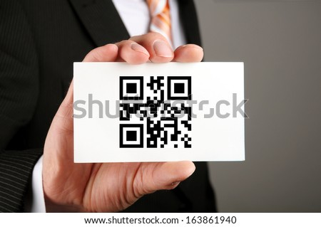businessman holding a card with qr code which means contact us - stock photo