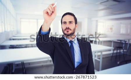Businessman holding a chalk and writing something against empty class room