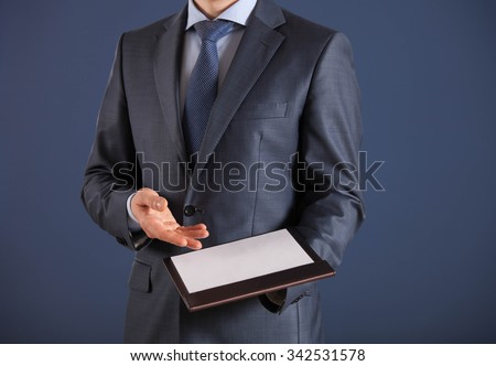 Businessman holding a clipboard with empty sheet of paper, dark  background