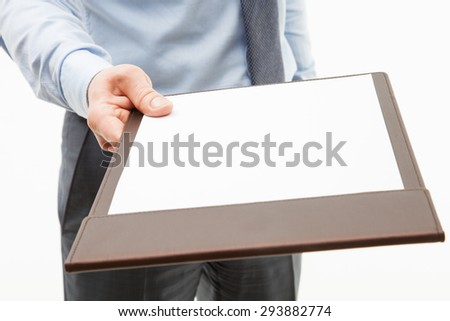 Businessman holding a clipboard with empty sheet of paper, white background