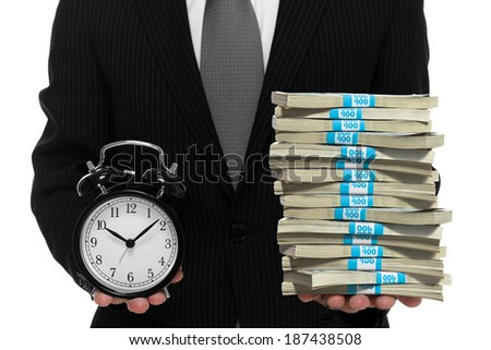 Businessman holding a clock and a stack of cash, concept of time is money - stock photo