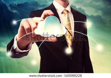 Businessman holding a cloud computing icon over cloudscape background - stock photo