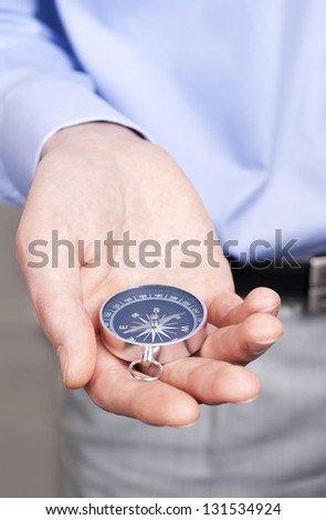 businessman holding a compass and chooses the direction to move - stock photo