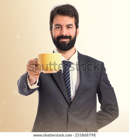 Businessman holding a cup of coffee over ocher background