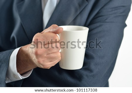 Businessman holding a cup of tea isolated on white - stock photo