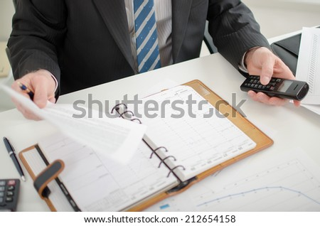 Businessman holding a document and a phone at his desk