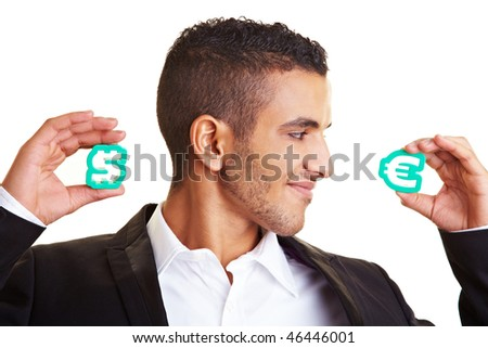 Businessman holding a Dollar and a Euro sign - stock photo