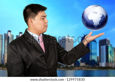 Businessman holding a globe - stock photo