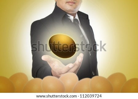 Businessman holding a golden eggs - stock photo