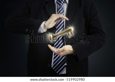 Businessman holding a golden key in his hands, symbolizing of success in business