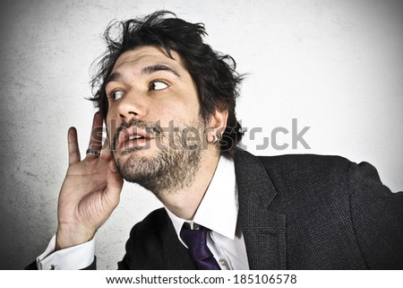 Businessman holding a hand to his ear