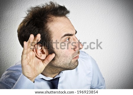 Businessman holding a hand to his ear  - stock photo
