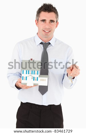 Businessman holding a key and a miniature house against a white background - stock photo