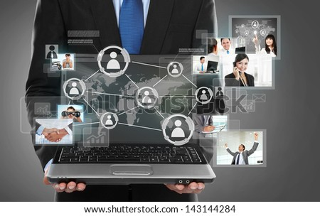 Businessman holding a laptop pc and surfing in the social network connection - stock photo
