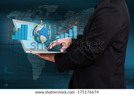 businessman holding a laptop showing business graph and globe on virtual screen