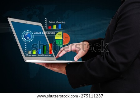 businessman holding a laptop showing business graph on virtual screen