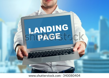 Businessman holding a laptop with an landing page. Business, technology, internet and networking concept. - stock photo