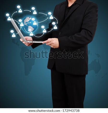Businessman holding a laptop with social network icons coming out