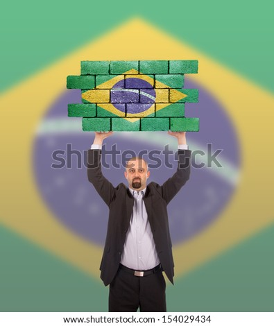 Businessman holding a large piece of a brick wall, flag of Brazil, isolated on national flag - stock photo