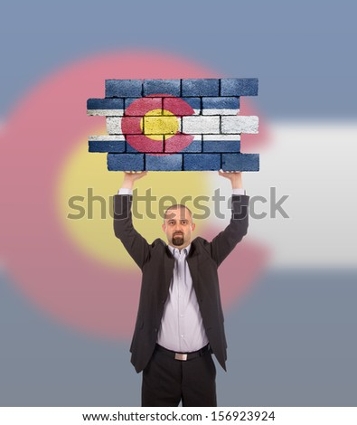 Businessman holding a large piece of a brick wall, flag of Colorado, isolated on national flag - stock photo