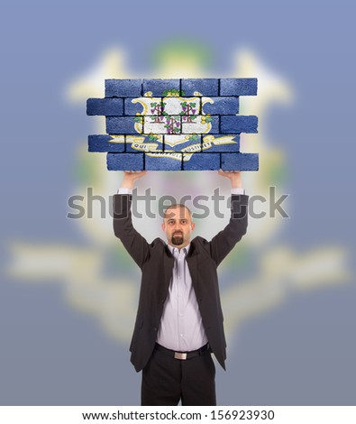 Businessman holding a large piece of a brick wall, flag of Connecticut, isolated on national flag - stock photo