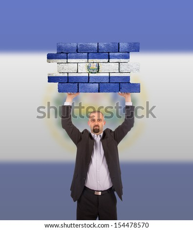 Businessman holding a large piece of a brick wall, flag of El Salvador, isolated on national flag - stock photo