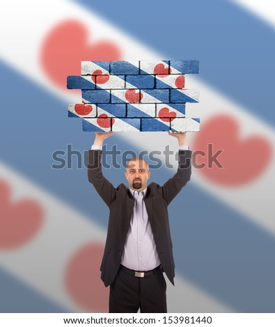 Businessman holding a large piece of a brick wall, flag of Friesland, isolated on national flag - stock photo